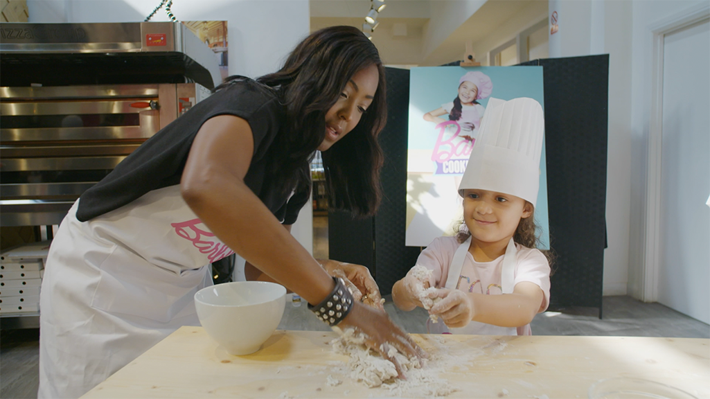 Angelica Bell cooking pizza at a Barbie event.